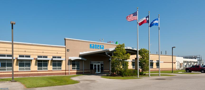 Exterior photo of the front of the Kaneka facility with an American flag, Texas flag, and Kaneka flag out front.