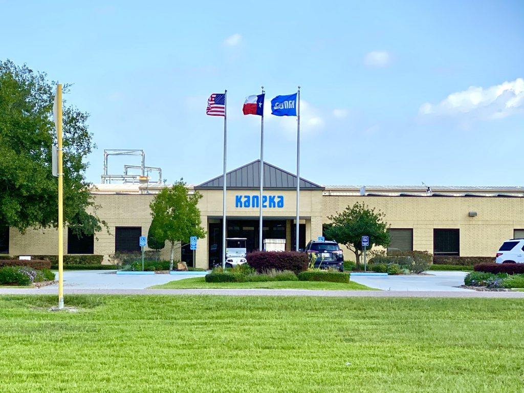 Centered photo of the front of the entrance to the Kaneka building with a green lawn in the foreground and three flagpoles out front with an American flag, a Texas flag, and a Kaneka flag.